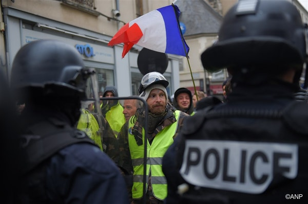 A protester wearing a yellow vest (gilet jaune) faces French police officers during an anti-government demonstration called by the Yellow Vest movement, in Bourges, on January 12, 2019