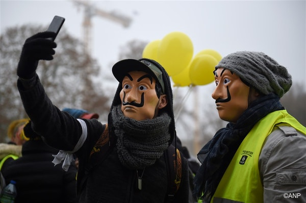 """Protesters wearing """"Casa de Papel"""" masks and a yellow vest (gilet jaune), take a selfie picture during an anti-government demonstration called by the Yellow Vest movement, in Bourges, on January 12, 2019."""