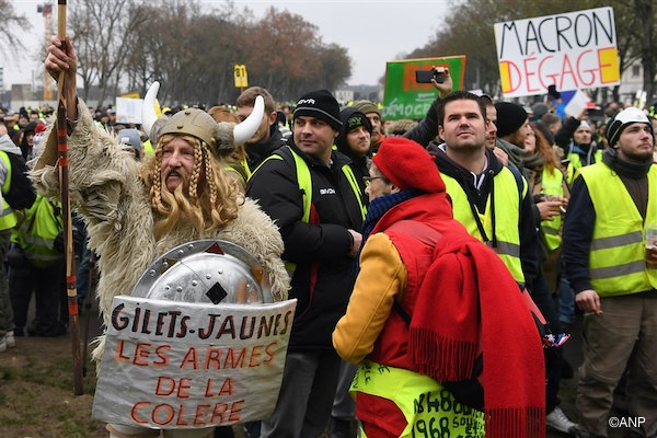 """A demonstrator (L) dressed as a Gaul holding a spear and a shield with a message reading """"Yellow Vests - Weapons of Wrath"""" during an anti-government demonstration called by the Yellow Vests """"Gilets Jaunes"""" movement, in Bourges on January 12, 2019."""