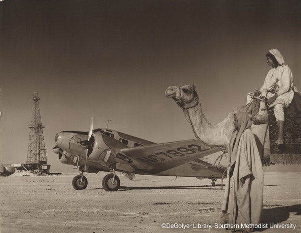 Oil well drilling rig in desert taken with airplane and men with camel, Arabian American Oil Co., Saudi Arabia, 1948
