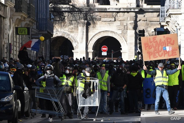 """A masked demonstrator holds a placard reading """"Power to the People"""" as he and others face anti-riot police in a street heading to the Arena of Nimes in background during an anti-government demonstration called by the Yellow Vests """"Gilets Jaunes"""" movement, in Nimes, southern France on January 12, 2019. France braced for a fresh round of """"yellow vest"""" protests on January 12, 2019"""