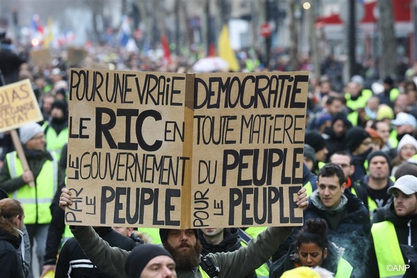 """A demonstrator holds a placard reading """"for a true democracy the RIC (for """"Citizens' Initiative Referendum"""") on any matter, the government of the people, by the people, for the people"""", in Paris, during an anti-government demonstration called by the Yellow Vest """"Gilets Jaunes"""" movement, on January 12, 2019."""