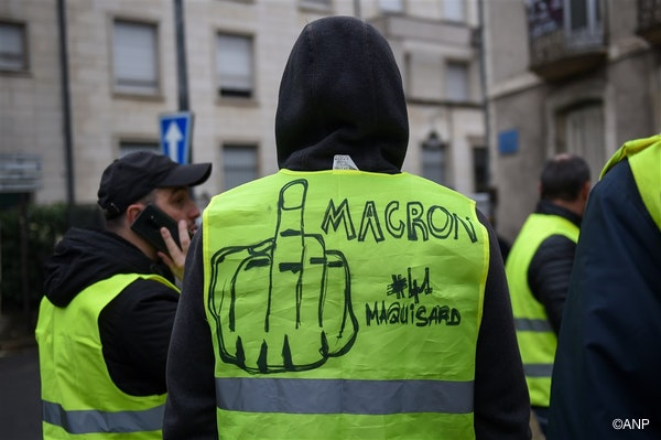 A man wears a yellow vest (gilet jaune) on which is written 'Macron (French President)' next to a drawing of a finger during an anti-government demonstration called by the Yellow Vest movement, in Bourges, on January 12, 2019.